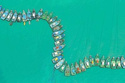 Рибарски лодки образуват вълна във водата.