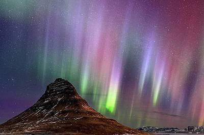 Планината Киркхуфел, ИсландияСветлината на северното сияние струи над планината Киркхуфел на исландския полусторов Снайфедлснес.
