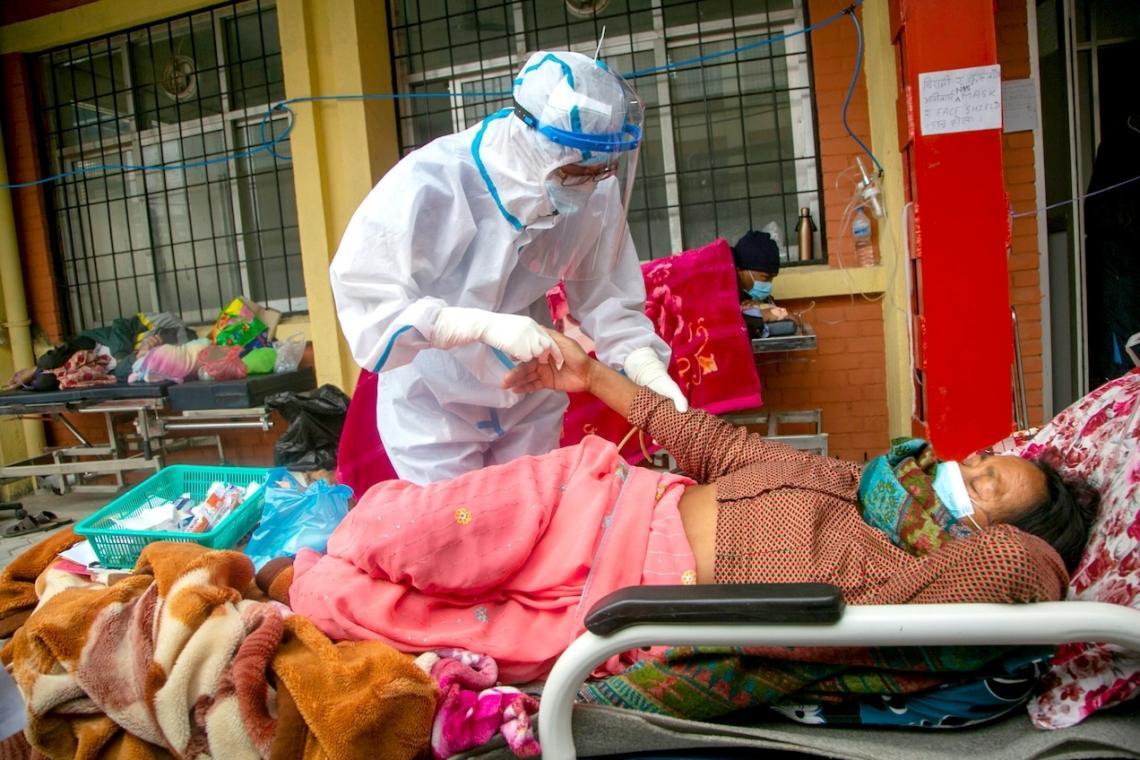 В разгара на пандемията непалски санитари оказват помощ на пациент с Covid-19 пред спешното отделение на правителствена болница в Катманду.