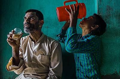 60-годишният Махамад Али Молла, който ослепял на 46 г., зависи от грижите народнините си, включително и на внука си (вдясно), в Западен Бенгал, Индия....