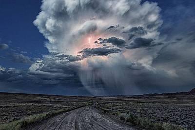 Голям кълбесто-дъждовен облак, прорязан от светкавица, осветява небето по време на буря и сипе дъжд над източните равнини на Уайоминг.