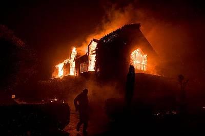Пламъци поглъщат сграда край лозя в Напа, Калифорния в понеделник.Близо 3 500 души са изгубили бизнеса и домовете си в пожарите.