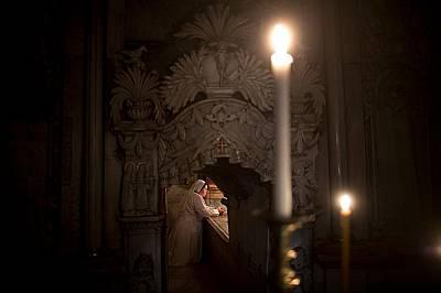 Монахиня коленичи в молитваМонахиня коленичи в молитва пред погребалното ложе на Христос в едикулата.