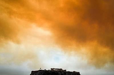 Партенонът, древният акропол в Атина, Гърция, се издига на фона на кълба дим от пожара в Кинета, близо до Атина.