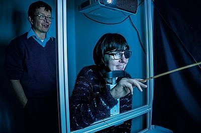 Риан Люис, на 50 г., използва показалка, за да интерпретира изображенията, които ретиналният й имплант изпраща към мозъка й, докато оптометристът Чарл...