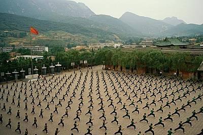 Деца учат кунг фу в провинция Хенан, Китай. Червеният фон на китайското знаме е символ на комунистическата революция от 1949 г. Четирите малки звезди...