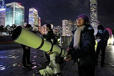 Любител наблюдава Луната от Виктория Харбър в Хонг Конг