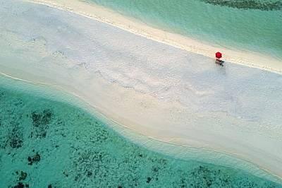 Островен бряг на МалдивитеСамотен червен чадър на островен бряг на Малдивите. Снимката е направена с дрон.