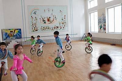 Деца се учат да карат едноколесни велосипедиДеца в детска градина се учат да карат едноколесни велосипеди във физкултурен салон в Пхенян.