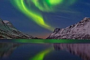 Тромсо, НорвегияФиорд отразява зелената светлина на северното сияние край Тромсо, Норвегия.