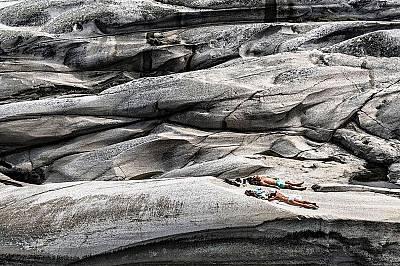 Момче и момиче се пекат на слънце върху гладките скали на Верденс Енде, Норвегия.