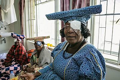 Жени от племето хереро (традиционните им шапки напомнят за рогата на кравите – жизненоважни в тяхната култура) очакват да им свалят превръзк...