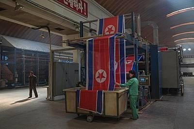 Работничка в текстилна фабрика подрежда ролки със севернокорейското знаме.