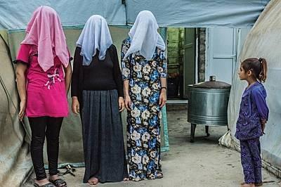 Момиченце гледа, докато дъщеря (вляво), нейната майка (в средата) и зълва й биват снимани със скрити лица. Жените са язиди, етническо кюрдско малцин...