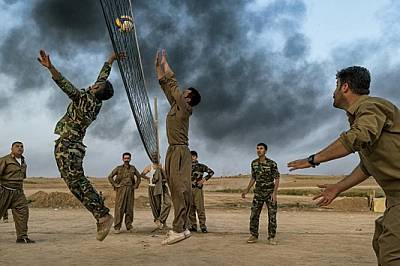 Южно от Киркук кюрдски войници пешмерга играят волейбол зад фронтовата линия. Когато през 2014 г. бойците на ИДИЛ, сред които се смята, че има и бив...