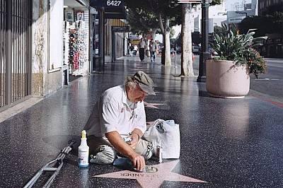 Мъж без крака чисти звезди от Алеята на славата в ХоливудМъж без крака чисти звезди от Алеята на славата в Холивуд. Литъл смята, че тази снимка предст...