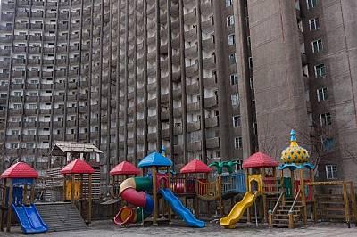 Детска площадка на фона на мрачни блоковеМрачни блокове се извисяват над шарена детска площадка в Пхенян. Гутенфелдър казва, че въпреки дългото работн...