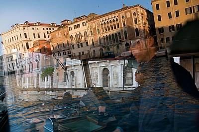 """Неуморните """"водни автобуси"""" vaporetto обикалят по Големия канал, който се отразява в прозореца на кабината, докато гондолите (остан..."""