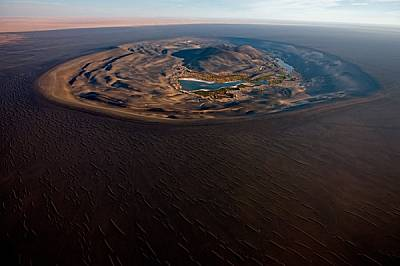 В сърцето на Сахара водата от паднали преди хиляди години дъждове изпълва вулканичния кратер Уау ан Намус. Вятърът разнесъл черна пепел от последното...
