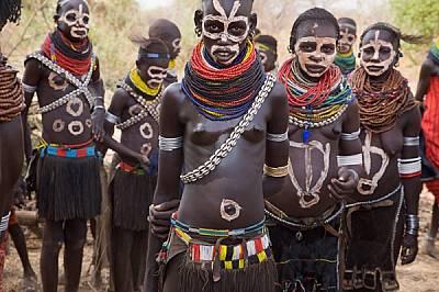 С боядисани с глина лица и нанизи с мъниста около вратовете, жени от племето нянгатом се готвят да танцуват на церемония край брега на река Омо. Търже...