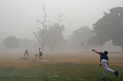 Мъже играят крикет въпреки тежкия смог на 6 ноември.