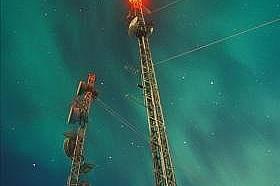 Телефонни кули на фона на ярко сияние над Юкон, Канада
