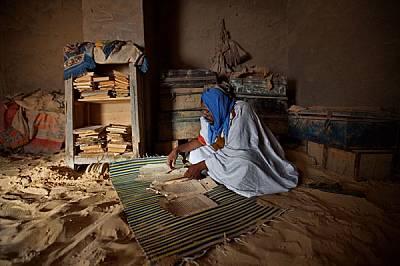 Имамът Чафи разглежда ръкописите на рода си, след като дъжд срутил покрива. Десетки семейства в Тимбукту получават помощи, за да съхраняват библиотеки...