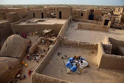 С пера, направени от стебла от пустинни храсти, Бубакар Садек (в бяло) преподава калиграфия на покрива на своето студио. Някога градът издържал процъф...
