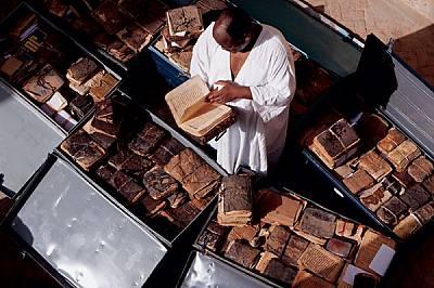 Ислямският книжовник Абдел Кадер Хайдара подрежда сандъци с некаталогизирани ръкописи, които се пазят в дома му и са част от родовото съкровище от 22...