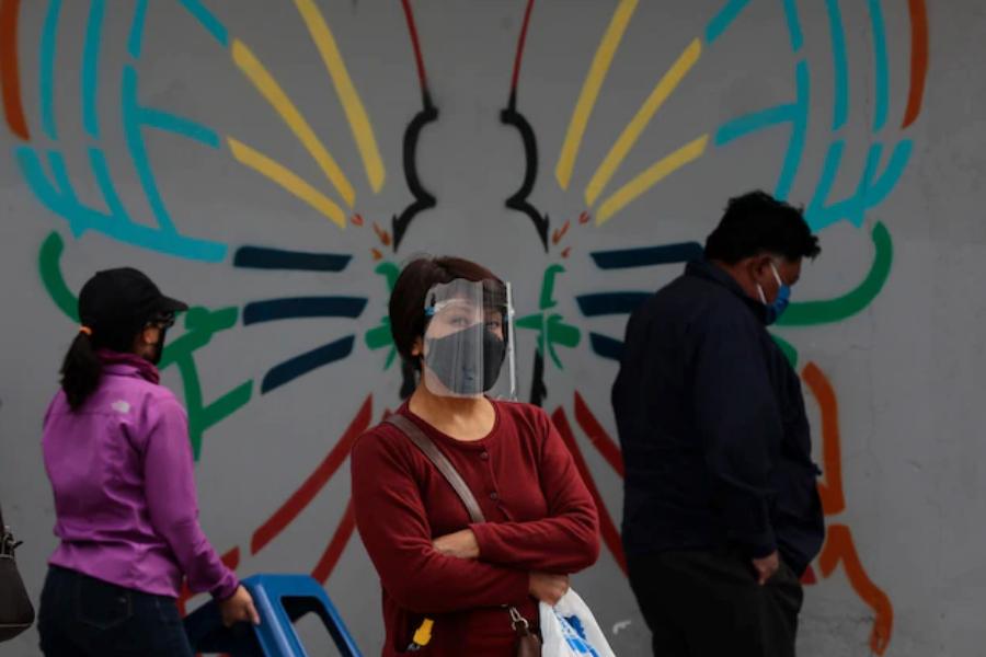 Жена носи пластмасова защитна маска, докато чака да се ваксинира за COVID-19 в Кито, Еквадор, 8 юли 2021 г.