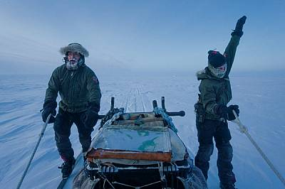 Въртейки ръцете си в кръг, за да се стоплят, Йеспер Олсен (вдясно) и Расмус Йоргенсен се плъзгат на ски до пълната с провизии шейна: пушки,...