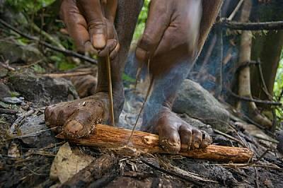 Притиснал с крака пръчка с подложка от прахан, мъж от племето пали лагерен огън върху влажната земя. Разпалването на огън с триене се практ...