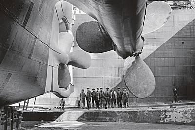 """Огромните винтове на """"Олимпик"""" - почти идентичен близнак на """"Титаник"""" - се извисяват над работниците..."""
