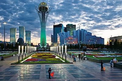 """""""Байтерек"""", извисяващ се над централния булевард на Астана, свети в зелено на фона на облачното вечерно небе. Символ на..."""