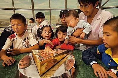 Посетителите нетърпеливо сравняват дланта си с масивния златен отпечатък от ръката на президента Нурсултан Назарбаев на панорамното ниво на...