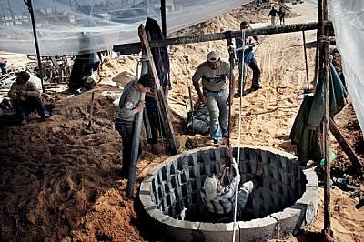 Собственик на нов тунел (с бялата шапка) гледа как синът му слиза в кладенеца, за да копае. Богатите могат да си позволят механични лебедки...