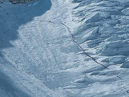 Множество алпинисти пъплят нагоре по стената на Лхотце на път към Лагер IV - последна спирка преди върха. Неясните регулации и бумът на комерсиалните...