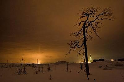 Факлите за изгаряне на газове и светлините на сондажната кула обгарят нощното небе над нефтеното находище Савуйское. Днес Русия е най-големият произво...