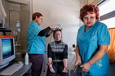 Медицински работници правят ЕЕГ на 38-годишната Надежда Гаскевич, която се подхлъзнала на лед преди десет години и още има нужда от редовно сканиране...