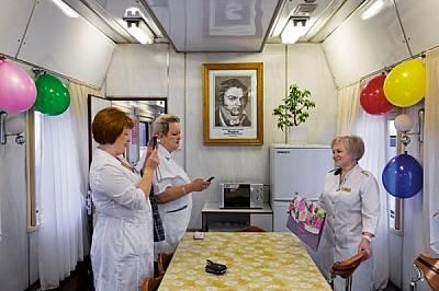 Две жени от персонала честитят рождения ден на медицинския директор Вера Шчербакова. На стената виси портретът на лекаря пионер от ХІХ в. Матвей Мудро...