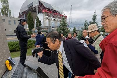 """Туристи (някои от тях живели край АЕЦ """"Фукушима"""") подпират гайгерови броячи на паметник, за да покажат, че блокира радиацията от ре..."""