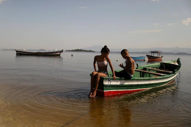 Деца си почиват на лодка край остров Пакета в залива Гуанабара в Рио де Жанейро по време на масово ваксиниране, част от усилията да се ваксинират...