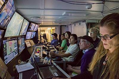 Учени и инженери в контролната зала на Falkor наблюдават действията на подводния апарат.