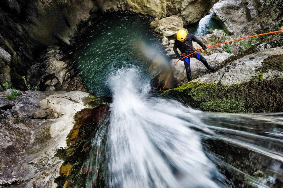 Мъж с оборудване за катерене, който се спуска по водопада в каньона.