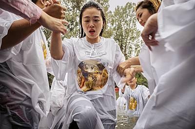 Индонезийска християнка излиза от водата след кръщението си в р. ЙорданИндонезийска християнка излиза от водата след кръщението си в р. Йордан, облече...