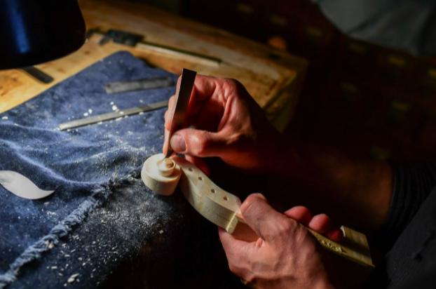 Млад лютиер работи над цигулка в работилница на майстор Джорджо Гризалес в Кремона, Италия.