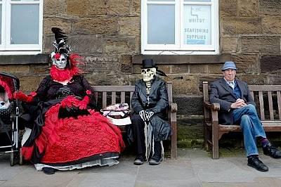 Екстравагантно облечени дами си почиват по време на фестивала.