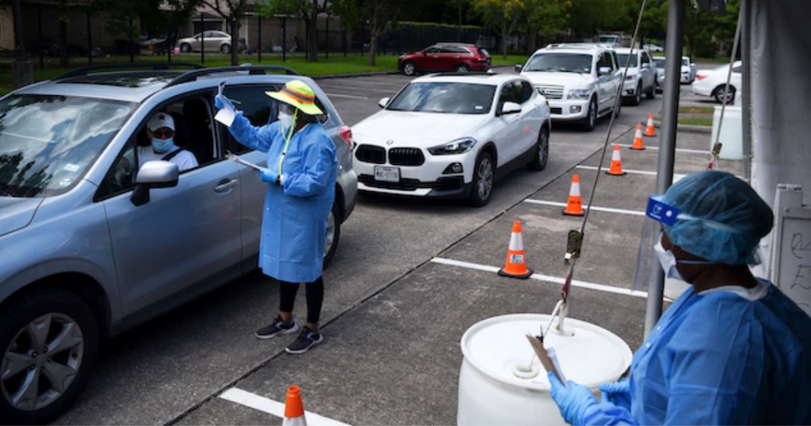 Здравен работник раздава тестове за COVID-19 на шофьори в Хюстън, Тексас.